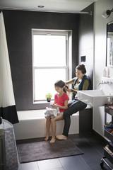 Mother tying hair of daughter in bathroom