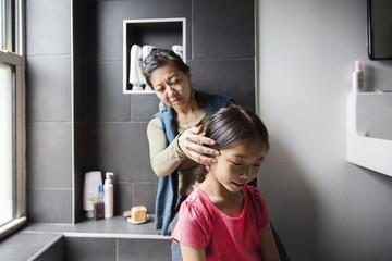 Mother grooming daughter in bathroom