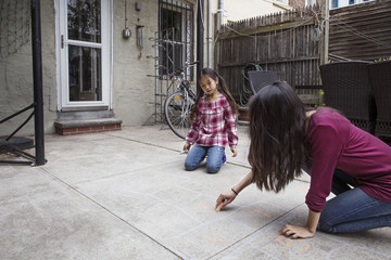 Girl looking at sister drawing hopscotch outside house