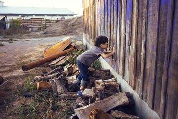 Side view of boy peeking through wooden wall