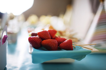 Close-up of strawberries and toothpicks in plate on table