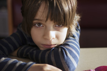 Portrait of boy resting on table at home