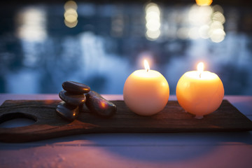 High angle view of illuminated candles and stones on table at health spa