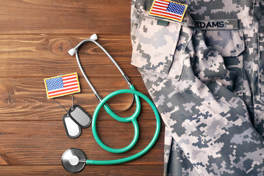 Military uniform with stethoscope and tags on wooden background