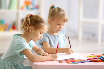 Adorable little sisters drawing and sitting at table