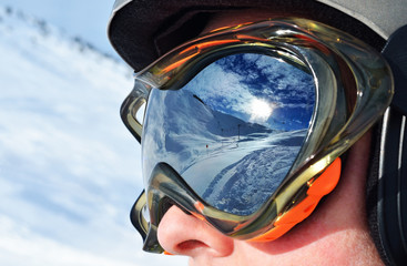Face of the skier in a ski mask with reflection of the winter mountain landscape. Selective focus