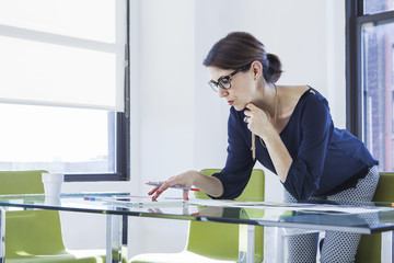 Businesswoman using tablet computer at conference table