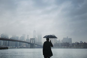 Rear view of man holding umbrella while looking at city view against cloudy sky