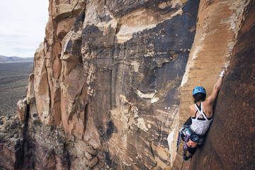 Young female hiker climbing rocky mountains at Red Rock Canyon National Conservation Area