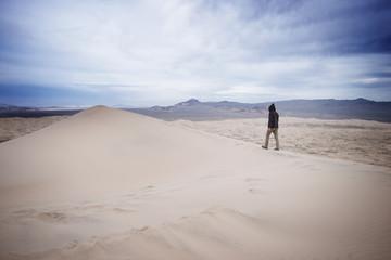 Man walking on sand dune in desert against cloudy sky