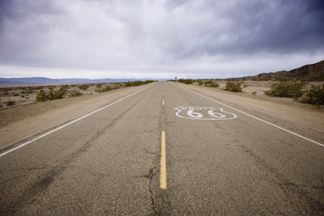 Route 66 sign on desert road against cloudy sky