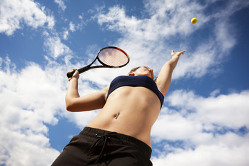 Low angle view of sporty woman playing tennis against cloudy sky
