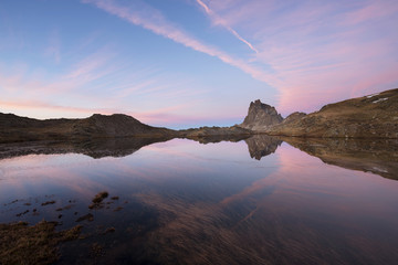 Scenic view of Pic du Midi d'Ossau by calm lake against sky during sunset