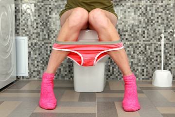 woman sits on toilet bowl