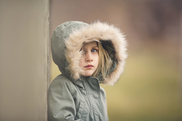 Portrait of thoughtful girl in fur hood standing against wall