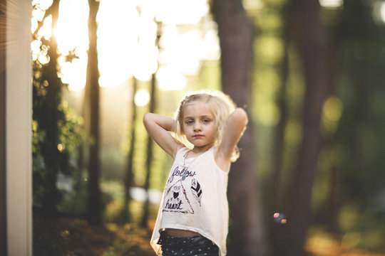 Portrait of girl relaxing against trees at yard