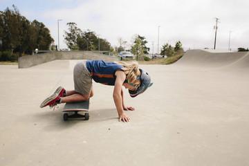 Playful girl kneeling on skateboard at park