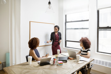 Confident businesswoman explaining strategy to female colleagues in board room