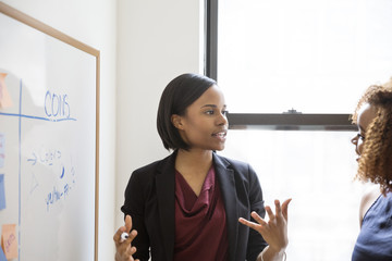 Confident businesswoman discussing with female colleague in board room