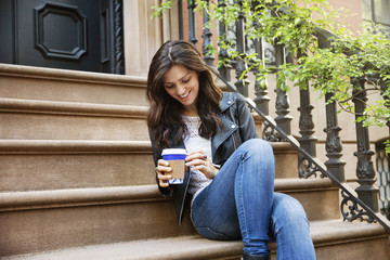 Happy woman holding disposable coffee cup while sitting on steps