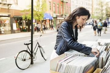 Young woman selecting magazine at market stall