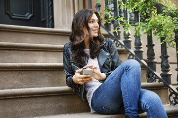 Thoughtful woman holding smart phone while sitting on steps