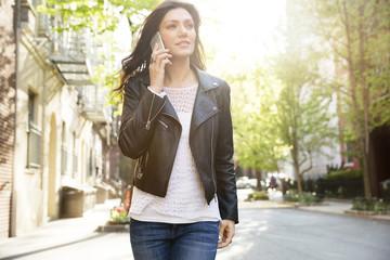 Beautiful woman answering smart phone while walking on street