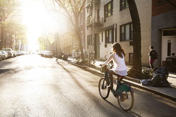 Rear view of young woman riding Citi bike on street