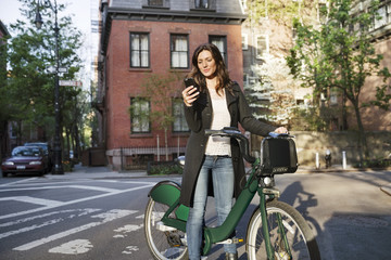 Young woman using smart phone while standing with Citi Bike on street