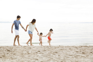 A happy family holding hands while walking on the beach