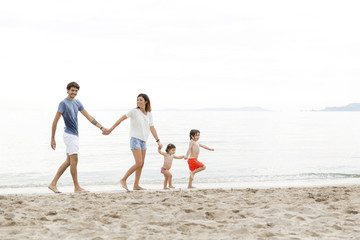 Happy family holding hands and walking at beach