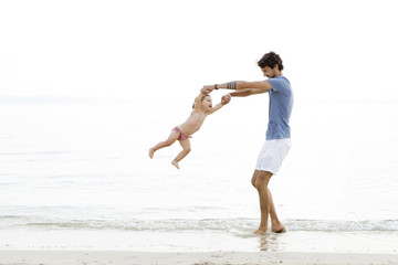 Happy father swinging daughter at beach
