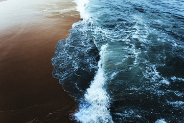 Overhead view of waves splashing on shore