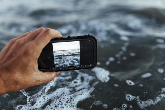 Close up of hand taking photograph of the sea with a smartphone