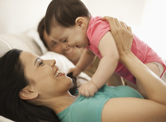 Mother playing with daughter while lying on bed at home