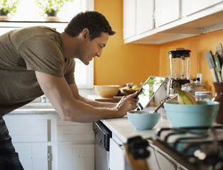 Smiling man using tablet while standing in kitchen at home