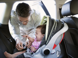 Baby crying while father locking car seat