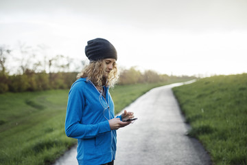 Female athlete using smart phone on road amidst grassy field