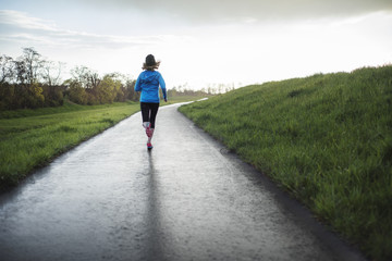 Full length of female athlete running on road amidst grassy field
