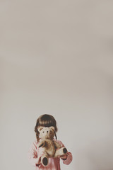 Girl holding teddy bear in front of face against white wall
