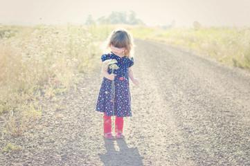 Full length of girl holding flowers on dirt road