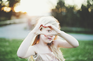 Portrait of girl making heart shape from hands at park