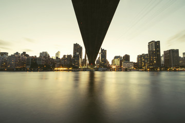 low angle view of Queensboro Bridge and illuminated skyline at dusk