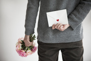 Men hide cute bouquets and letters behind