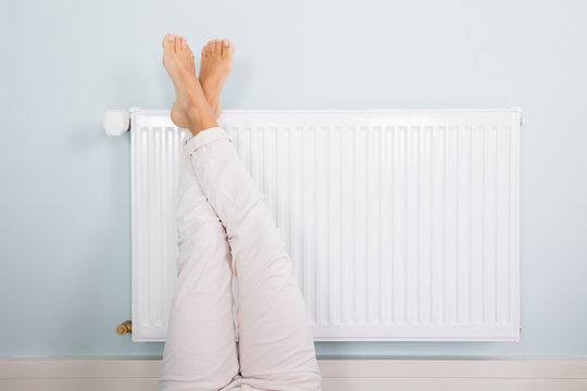 Woman Warming Up Her Feet On White Radiator