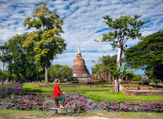 Woman with bicycle near temple in Thailand