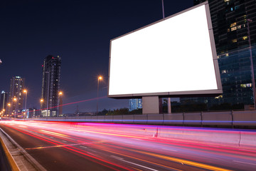 light trails, street and urban in the night with blank billboard for advertising business