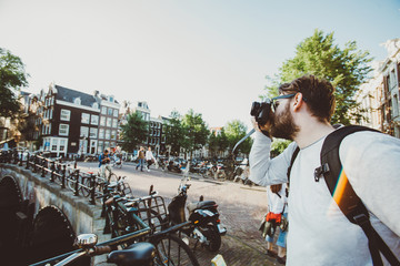 Tourist photographer takes selfie photo in Amsterdam, Netherlands. Tourist walks near canals on excursion and take photos for his blog.