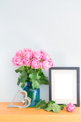 Violet fresh roses in vase with empty photo frame on wooden shelf