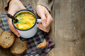 hands hold mug of vegetable soup